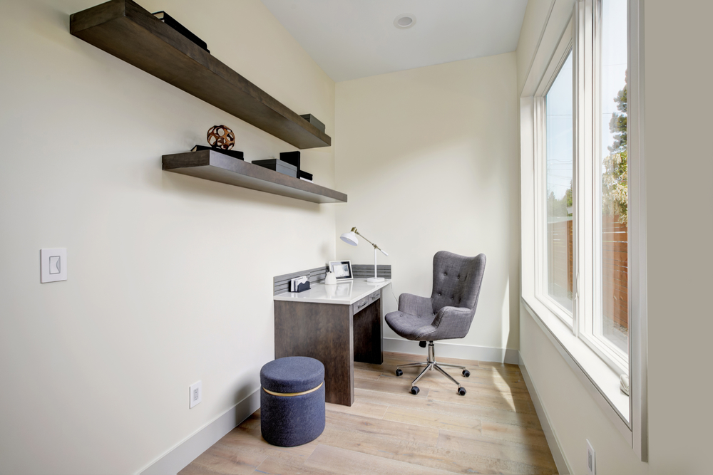 Light small home office interior with corner desk and grey upholstered chair atop hardwood floor. Northwest, USA
